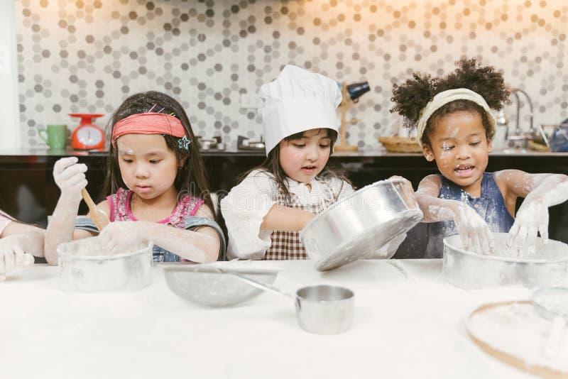 Grupa dzieciaki przygotowywa piekarnię w kuchni Dzieci uczy się kulinarni ciastka obrazy stock