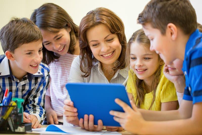 Grupa dzieciaki z nauczyciela i pastylki komputerem osobistym przy szkołą obraz royalty free