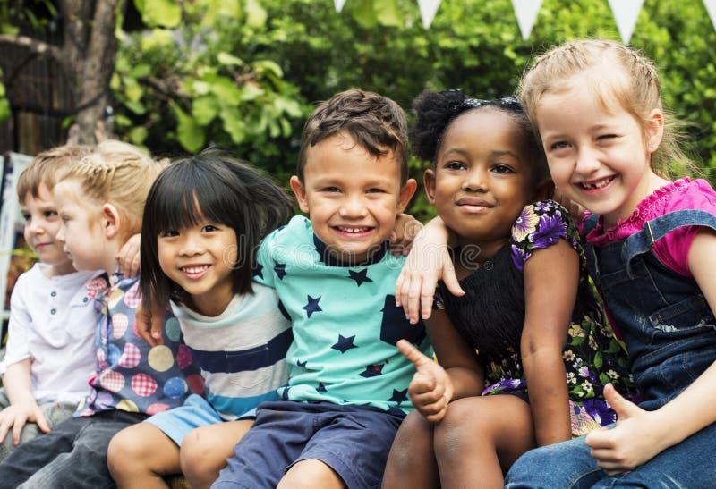Grupa dzieciniec żartuje przyjaciel rękę wokoło obsiadania i smilin fotografia stock