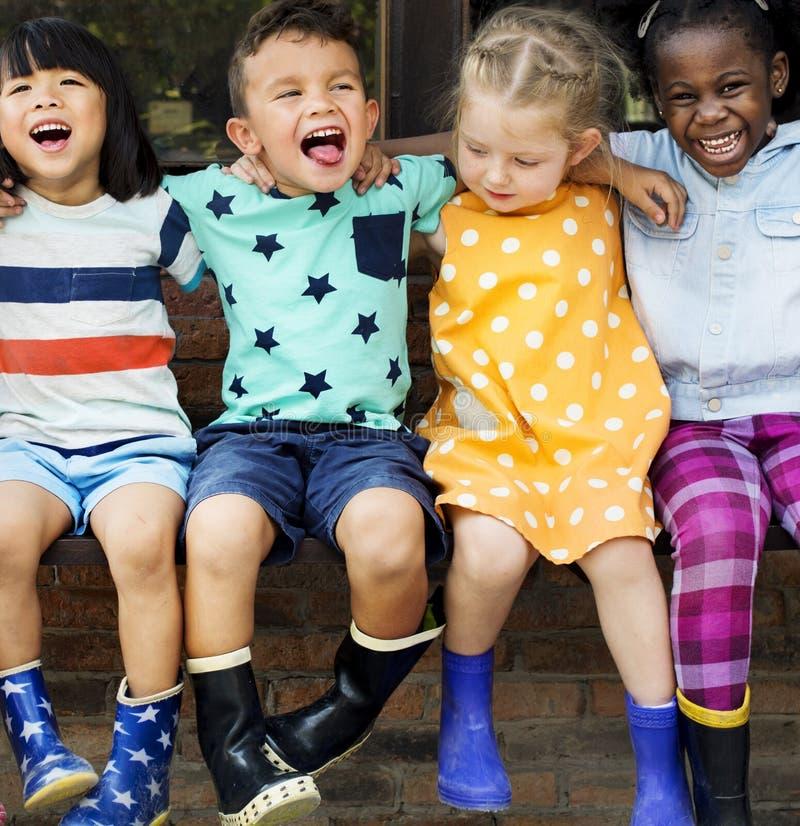 Grupa dzieciniec żartuje przyjaciel rękę wokoło obsiadania i smilin fotografia royalty free