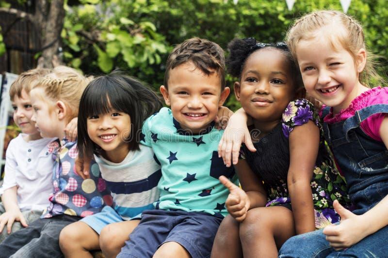 Grupa dzieciniec żartuje przyjaciel rękę wokoło obsiadania i uśmiechniętej zabawy zdjęcie stock