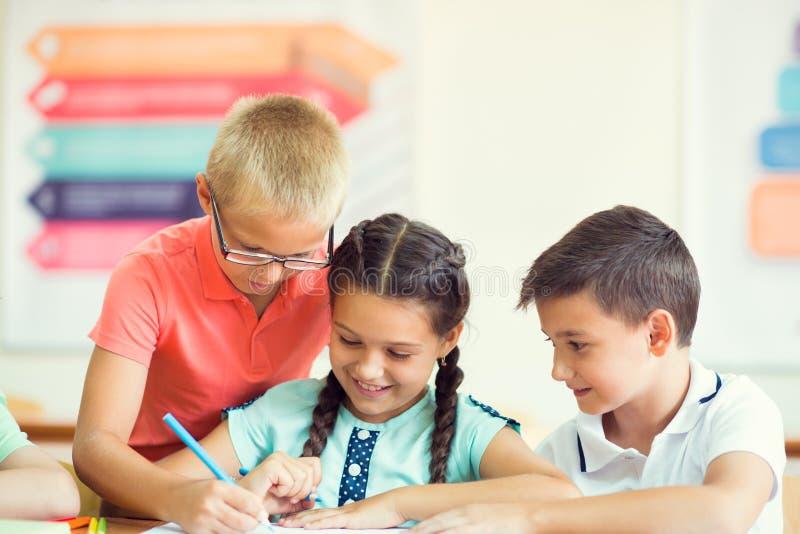 Grupa dziecko w wieku szkolnym uczy się przy klassroom w szkole zdjęcie royalty free