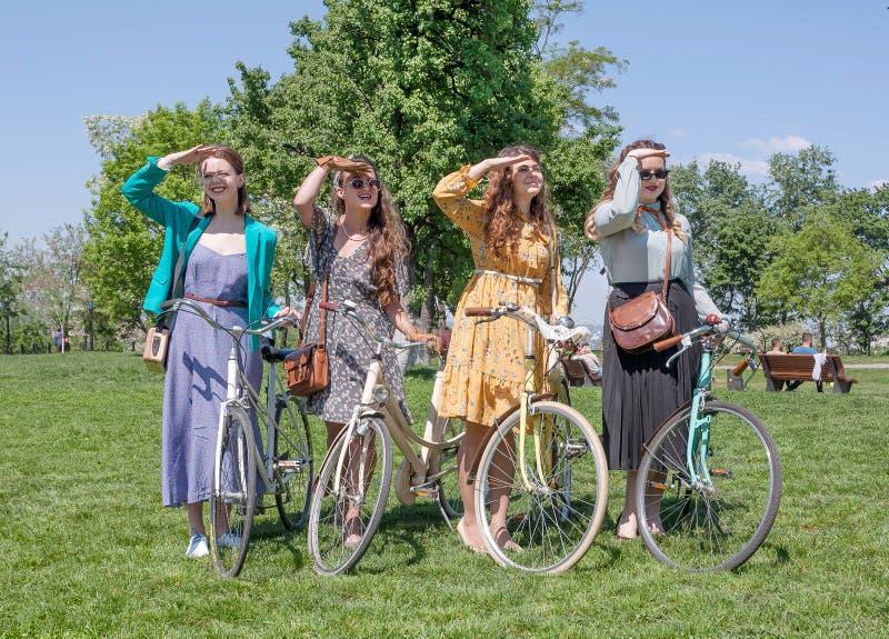 Grupa dziewczyny w starej modzie ubiera gotowego dla jeździć na rowerze z rocznika bicyklem podczas plenerowego festiwalu Retro r obrazy stock