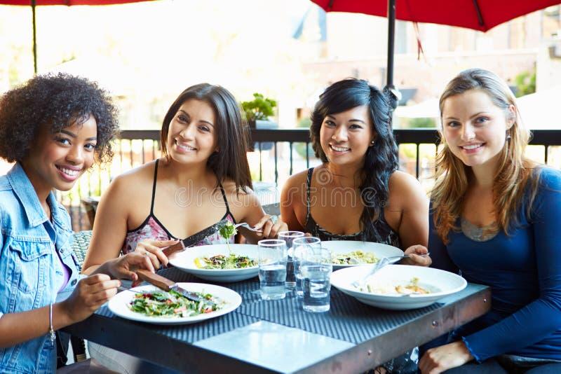 Grupa Żeńscy przyjaciele Cieszy się posiłek Przy Plenerową restauracją obraz stock