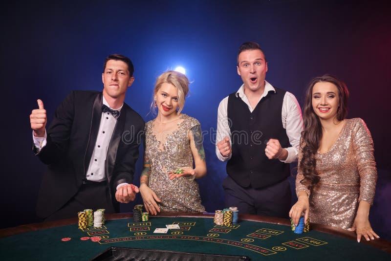 Grupa eleganccy bogaci przyjaciele bawić się grzebaka przy kasynem obraz royalty free