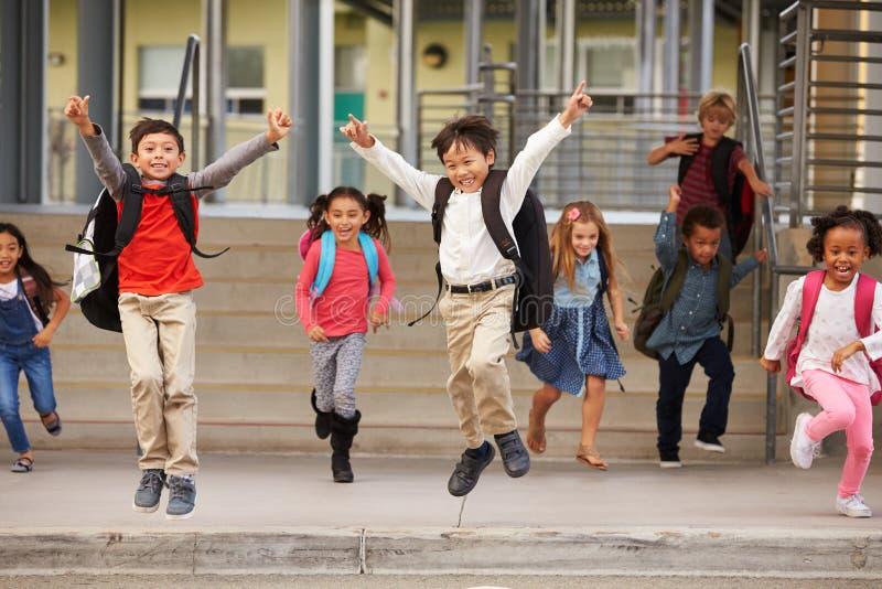 Grupa energiczna szkoła podstawowa żartuje opuszczać szkoły zdjęcia royalty free