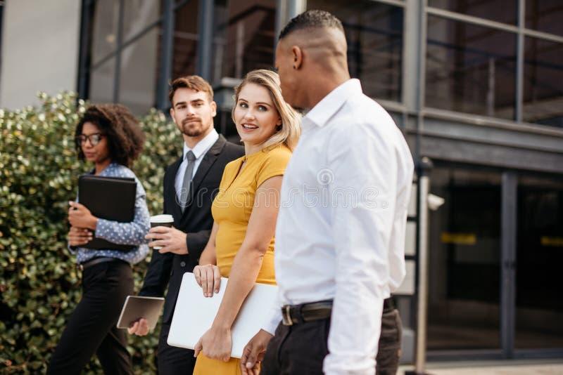 Grupa etniczni ludzie biznesu budzi się na zewnątrz biurowego buil obrazy stock