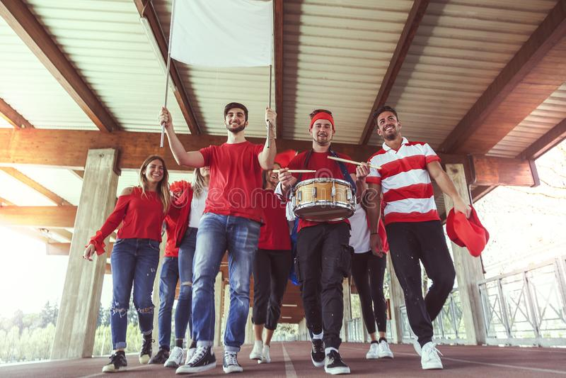 Grupa fan ubierał w czerwonego koloru odprowadzeniu pod dachem obraz royalty free
