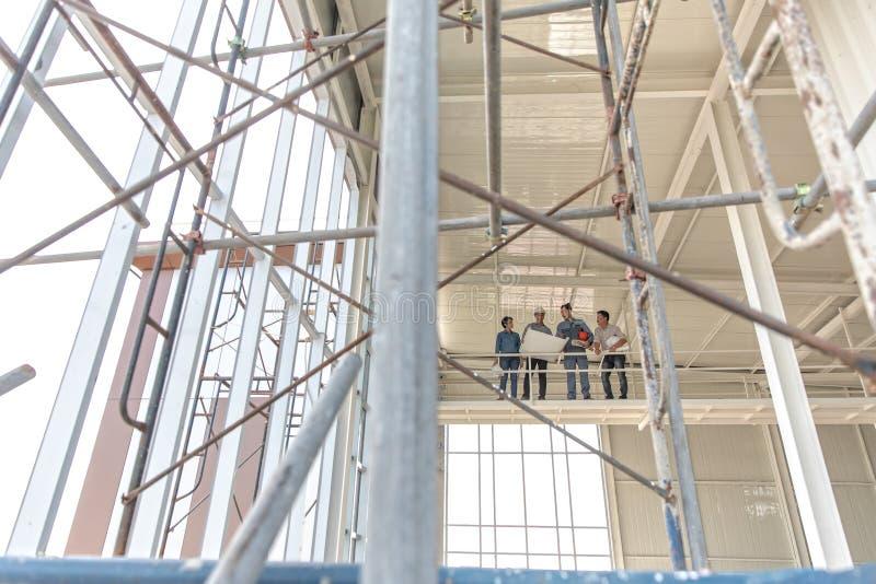 Grupa inżyniery mężczyzna i kobieta, pracujący wpólnie w budowie, stoi na moście wśród scarfold obraz royalty free