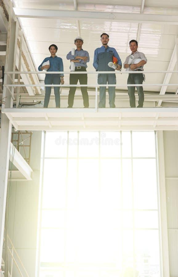 Grupa inżyniery mężczyzna i kobieta, pracujący wpólnie w budowie, stoi na moście wśród scarfold z światłem słonecznym obraz royalty free