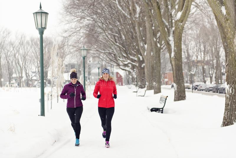 Grupa jogging w śniegu w zimie przyjaciele cieszy się zdjęcie royalty free