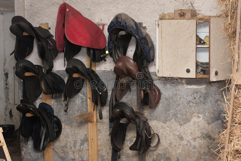 Grupa koń siodła hunging na ścianie w stajence fotografia royalty free