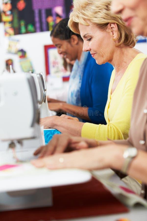 Grupa kobiety Używa Elektryczne Szwalne maszyny W klasie obraz royalty free