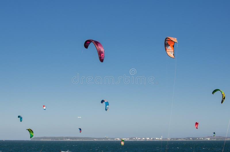 Grupa lata na niebieskim niebie przy Brighton Le Piasek plażą na wietrznym dniu kolorowy kitesurfing zdjęcie royalty free