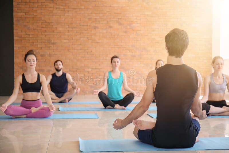 Grupa ludzi ćwiczy joga w gym obraz stock