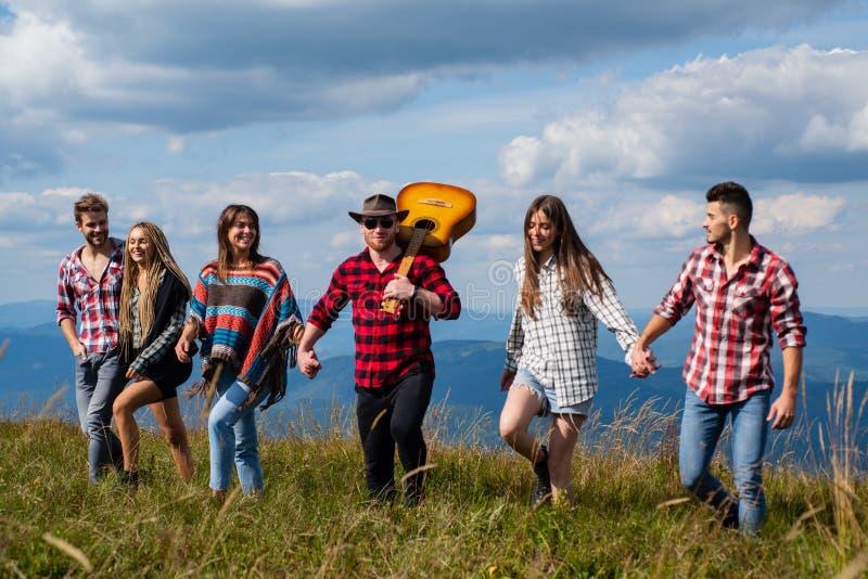 Grupa ludzi bawiących się w górach przeciwko górom Koncepcja podróży, przygody lub wyprawy Chodzenie grupowe Grupa obrazy stock