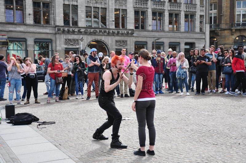 Grupa ludzi cieszy się ulicznego występ przy Dam Square, Amsterdam zdjęcia royalty free