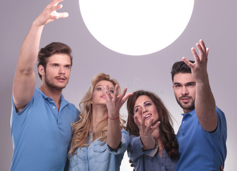Grupa ludzi dosięga out dla dużej piłki światło obraz stock
