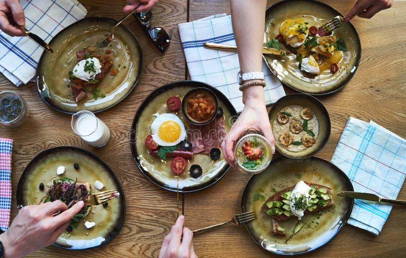 Grupa ludzi ma śniadanie i obsiadanie przy stołem, odgórny widok obraz stock