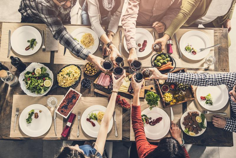 Grupa ludzi ma posiłek więź łomota wznoszący toast szkło obrazy stock