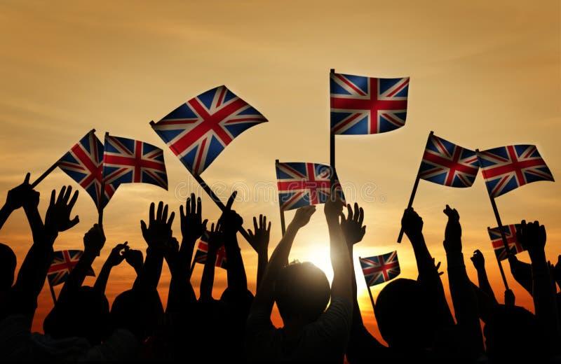 Grupa Ludzi Macha UK flaga w plecy Zaświecającym zdjęcia royalty free