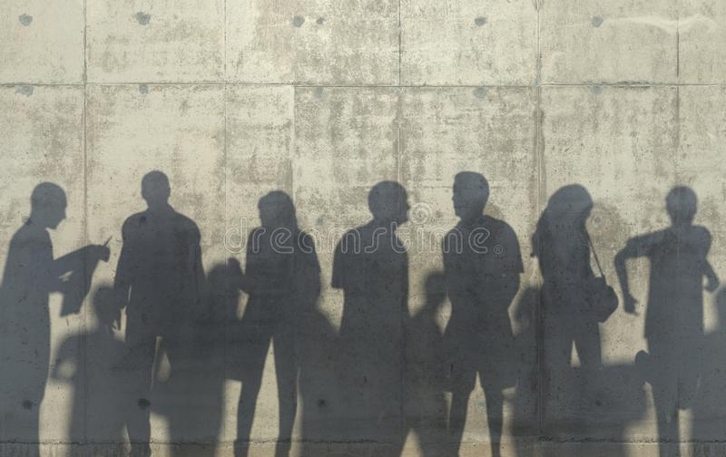 Grupa ludzi odprowadzenie w zrelaksowanej pozie ciska cień na betonowej ścianie Konceptualna kreatywnie ilustracja z sylwetkami fotografia stock