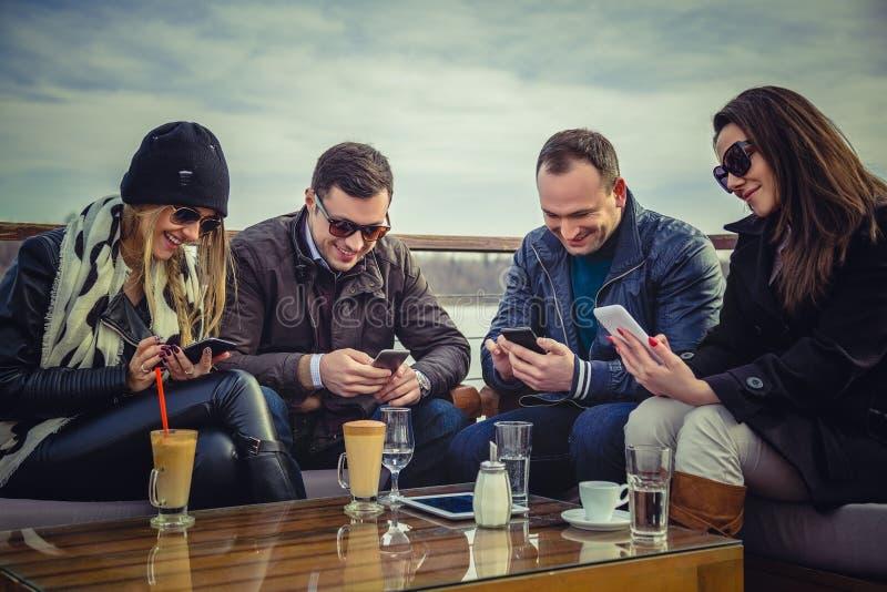 Grupa ludzi patrzeje śmiać się i telefon komórkowego zdjęcia royalty free