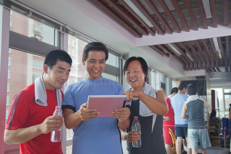 grupa ludzi patrzeje cyfrową pastylkę w gym zdjęcia royalty free