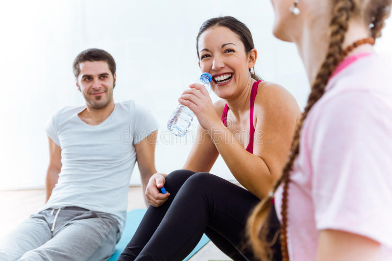 Grupa ludzi relaksuje na joga macie i opowiada po treningu s zdjęcia stock