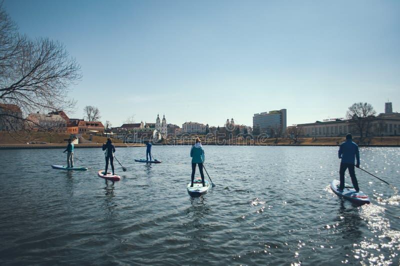 Grupa ludzi unosi się na paddle deskach w tle miasto, plenerowe aktywność na wodzie miasto Minsk fotografia royalty free