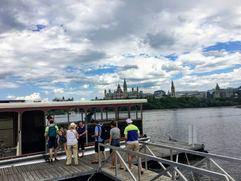 Grupa ludzi wsiada wodnego taxi w Gatineau, Quebec krzyżować Ottawa rzekę zdjęcie stock