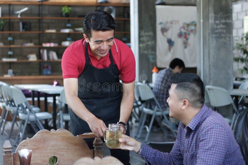 Grupa młody szczęśliwy przyjaciel otrzymywa jedzenie, napój od przy i kelnerów i serweru kawiarnią i restauracją żeńscy kelnery o zdjęcie royalty free