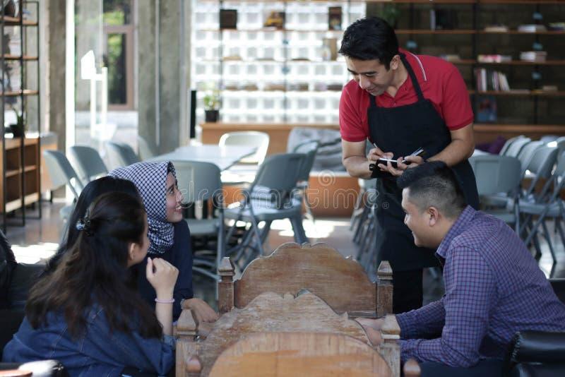 Grupa młody szczęśliwy przyjaciel rozkazuje od menu podczas gdy kelnery piszą rozkazach przy restauracją i kawiarnią zdjęcie stock