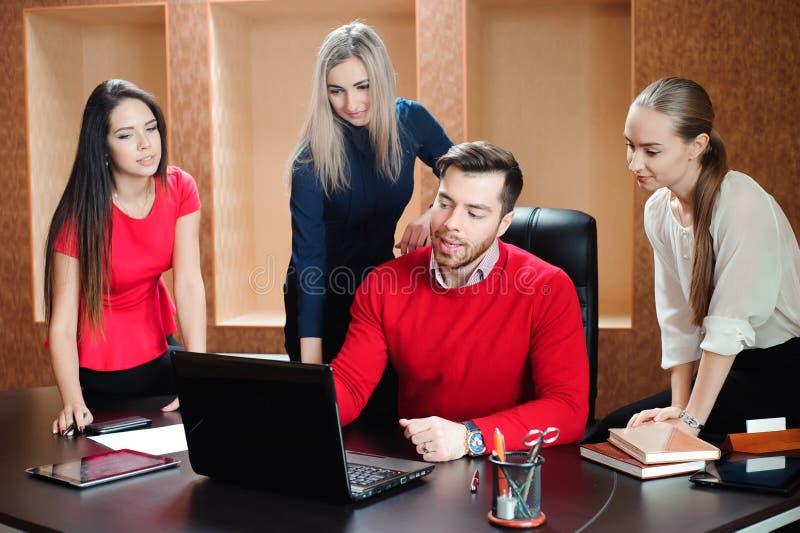 Grupa młodzi koledzy używa laptop przy biurem obrazy stock