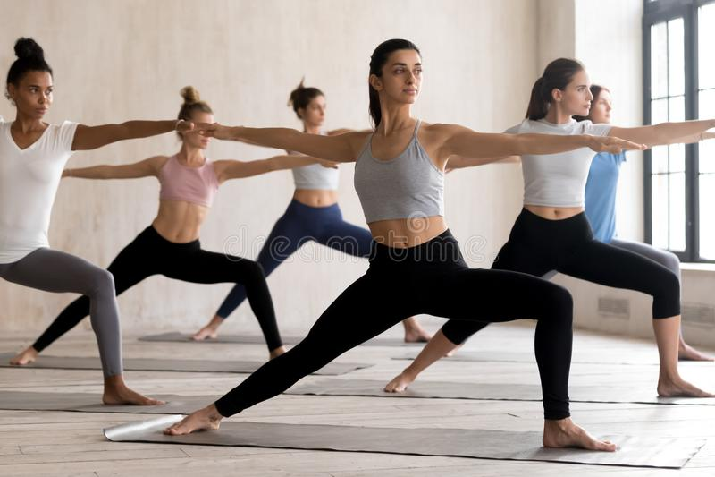 Grupa młodzi ludzie ćwiczy joga lekcyjnego robi wojownika 2 zdjęcia stock