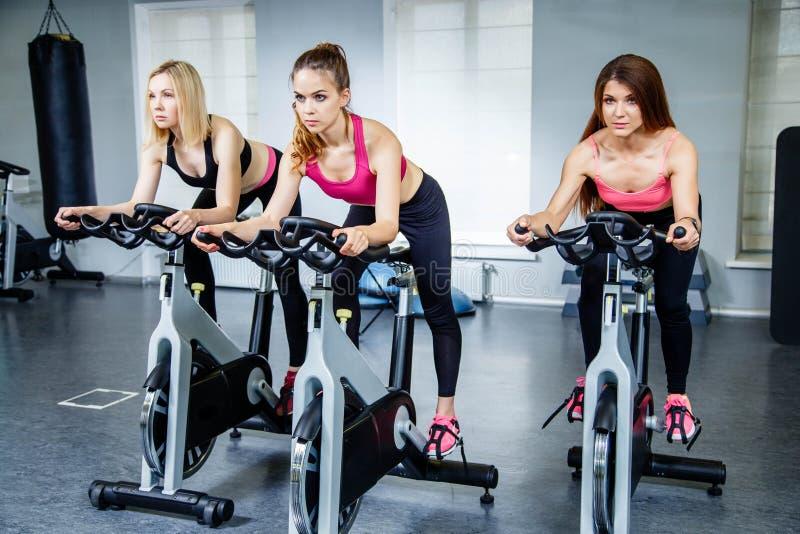 Grupa młode kobiety jeździć na rowerze w gym fotografia royalty free
