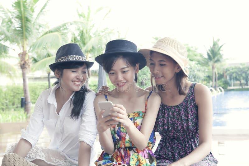 Grupa młody azjatykci kobieta przyjaciela dopatrywanie na mądrze telefonu ekranie zdjęcie royalty free