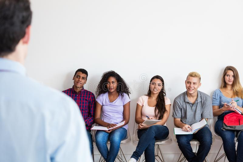 Grupa młody dorosły studencki słuchanie nauczyciel fotografia stock