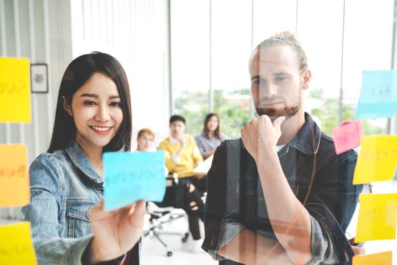Grupa młody pomyślny kreatywnie wieloetniczny drużynowy uśmiech i brainstorm na projekcie wpólnie w nowożytnym biurze Kobiety kle fotografia stock