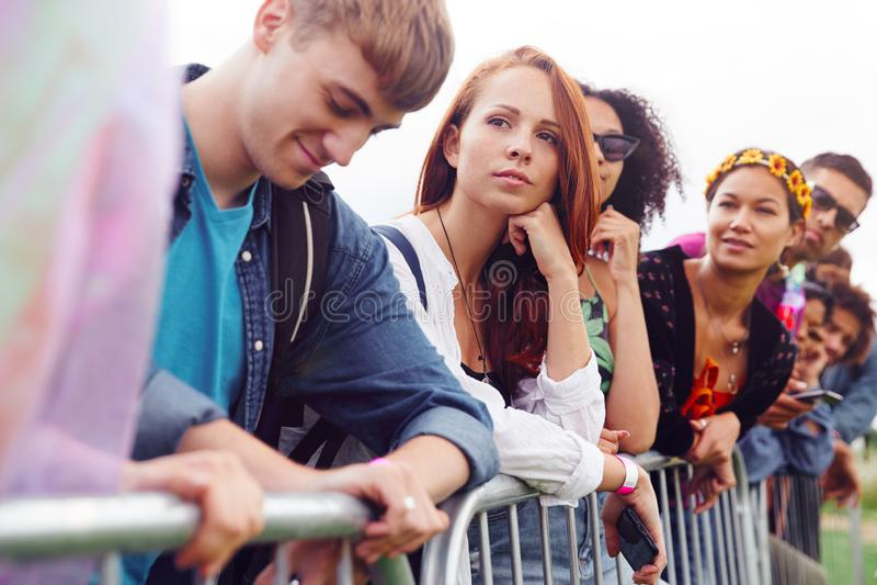 Grupa Młodych Przyjaciół Czekających Za Barierą Na Wejściu Na Stronę Festiwalu Muzycznego zdjęcie royalty free