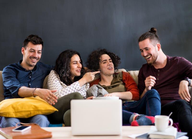 Grupa młodych znajomych z laptopem siedzącym na kanapie, oglądającym film obraz royalty free