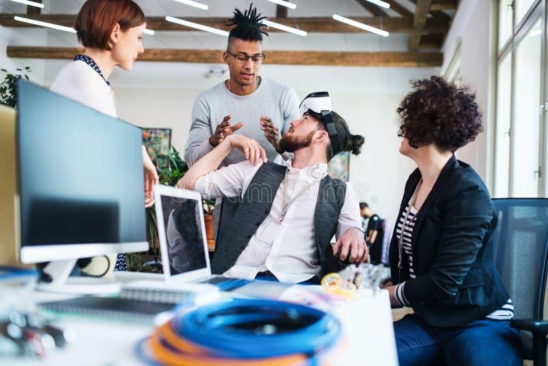 Grupa młodzi biznesmeni opowiada w biurze, uruchomienia pojęcie obraz royalty free