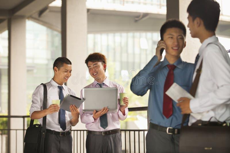 Grupa młodzi biznesmeni pracuje outdoors i dyskutuje, ono uśmiecha się zdjęcia stock