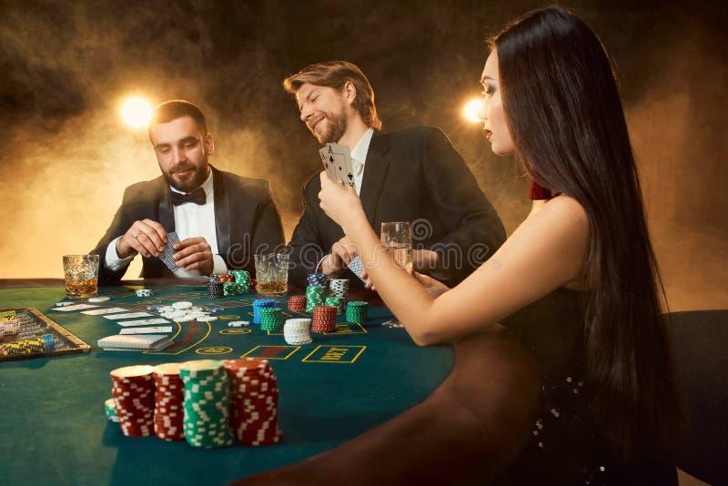 Grupa młodzi bogaci ludzie bawić się grzebaka w kasynie zdjęcia stock