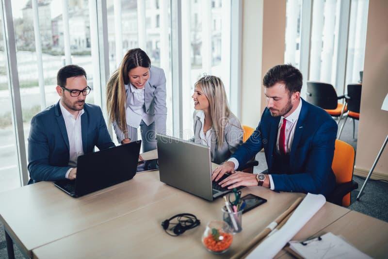 Grupa młodzi ludzie biznesu pracuje laptop i używa przy biurowym biurkiem podczas gdy siedzący wpólnie zdjęcie stock