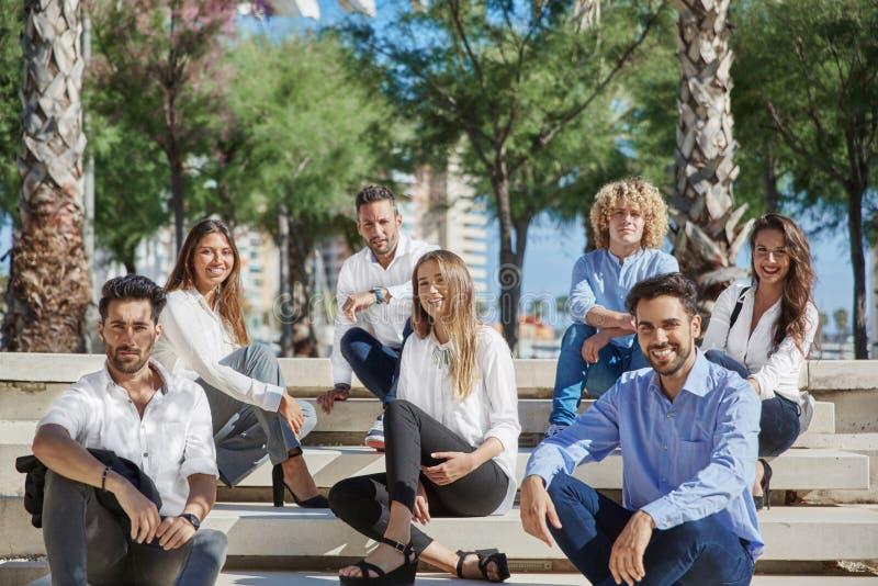 Grupa młodzi ludzie biznesu siedzi wpólnie outside ono uśmiecha się obrazy stock
