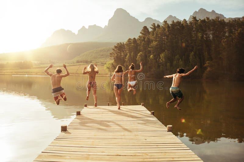 Grupa młodzi ludzie skacze w wodę od jetty obrazy stock