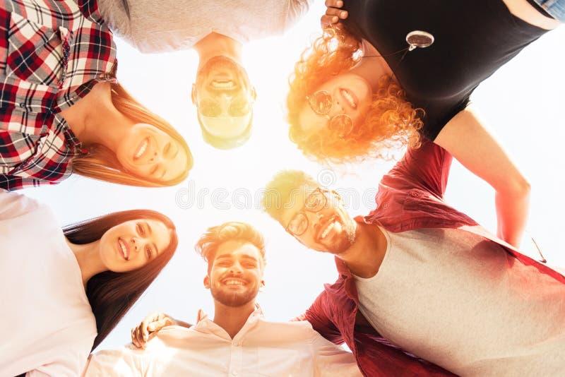 Grupa młodzi ludzie stoi w okręgu, outdoors