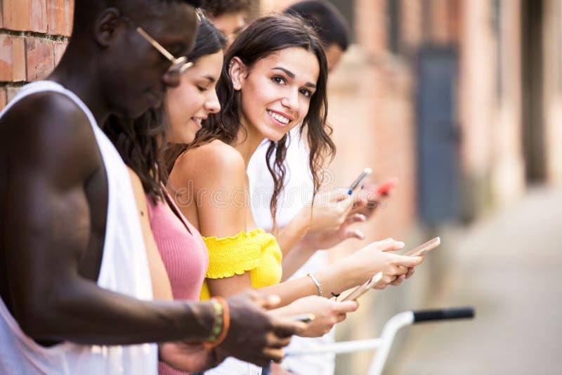 Grupa młodzi modnisiów przyjaciele używa mądrze telefon w obszarze miejskim zdjęcie stock
