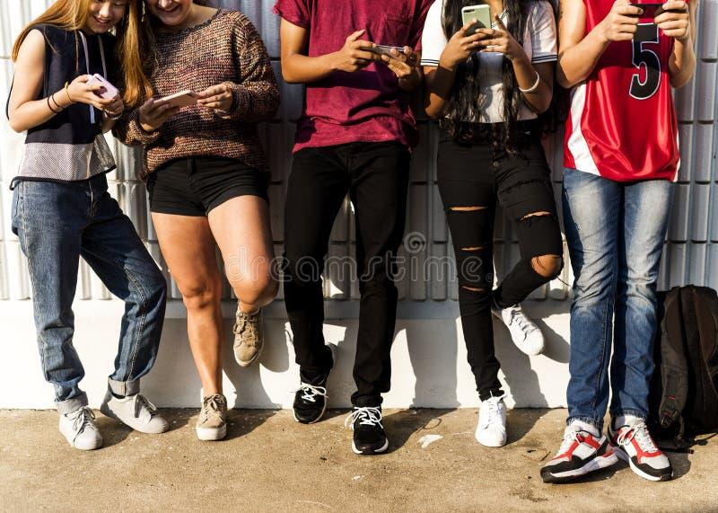 Grupa młodzi nastolatków przyjaciele chłodzi out wpólnie używać smartphone ogólnospołecznego medialnego pojęcie obrazy royalty free
